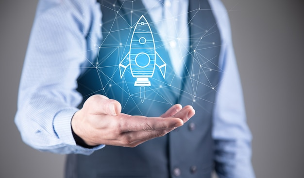 Start up concept with businessman holding abstract digital rocket