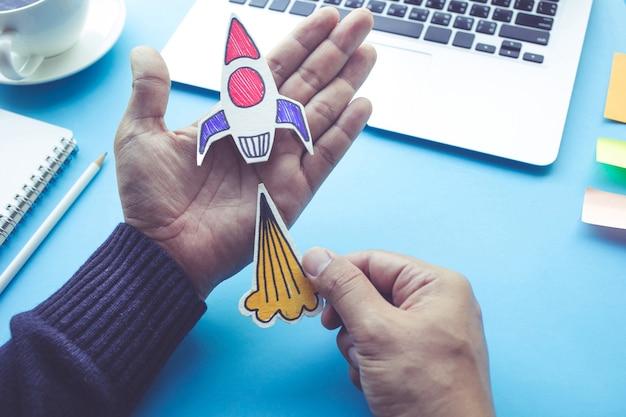 Концепция запуска с ракетой в мужской руке на синем столе