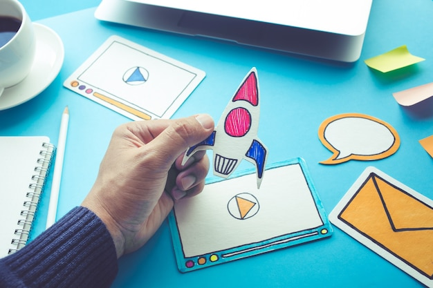 Start up concepts with rocket in male hand on blue desk table