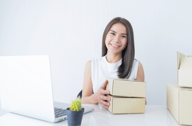 Start up small business entrepreneur sme or freelance woman holding boxes working at home concept