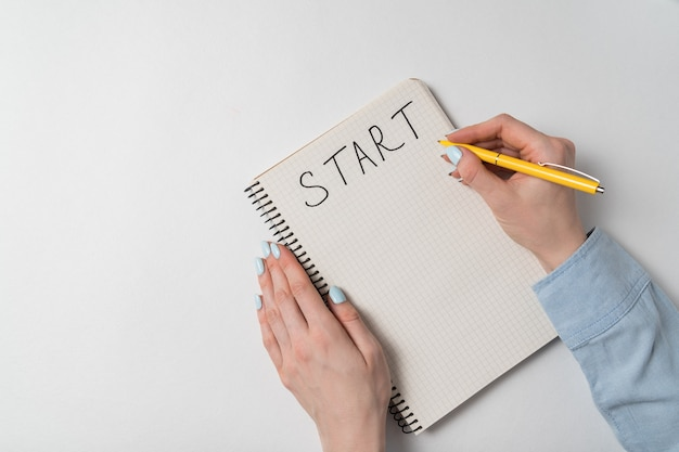 Start written on notebook over white background. female hand writing in notepad