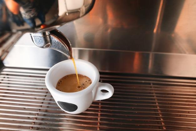 Начните день с чашки ароматного напитка. стильная черная машина для приготовления эспрессо, заваривающая кофе, снятая в кафе.