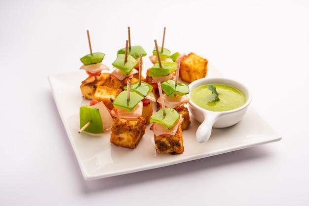 スタータースナックパニールティッカ、スティックインプレート、グリーンチャツネを白で分離。カッテージチーズのグリルと野菜とスパイスのインド料理