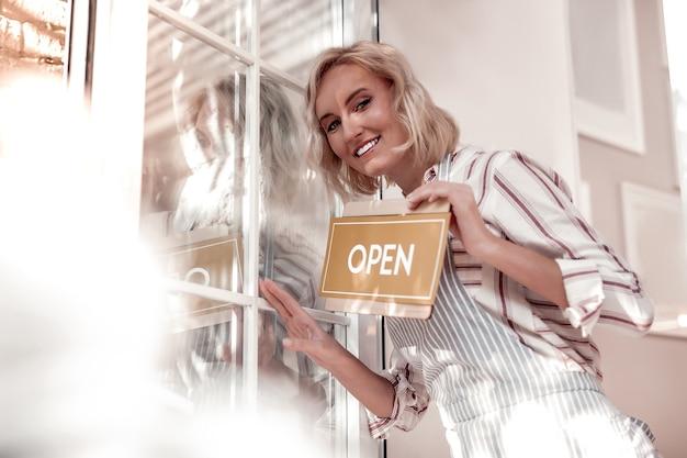 起業。自分の食堂を開いている間、オープニングサインを保持しているうれしそうな幸せな女性