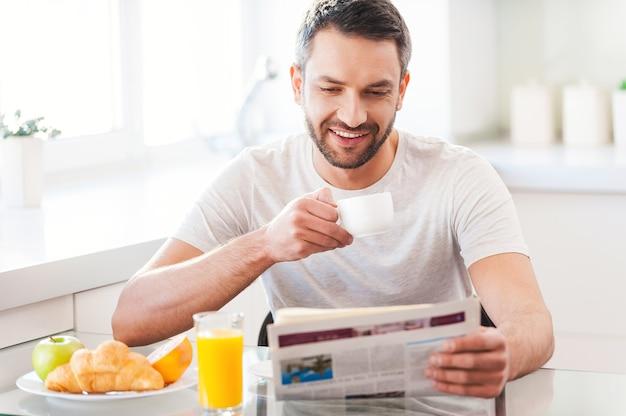 良いたよりからの始まり。新聞を読んで、コーヒーを飲みながら、キッチンで朝食をとっているハンサムな若い男