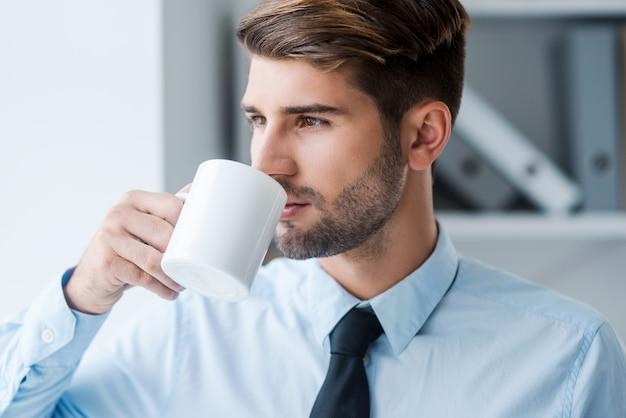 淹れたてのコーヒーで一日を始めましょう。コーヒーを飲むシャツとネクタイの思いやりのある若い男
