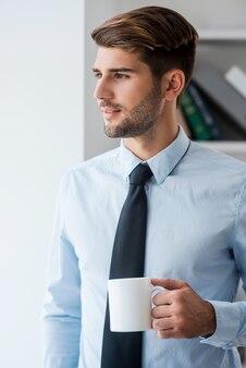 淹れたてのコーヒーで一日を始めましょう。コーヒーカップを保持しているシャツとネクタイの思いやりのある若い男