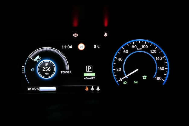 Starting electric car dashboard. track in to the button. finger press the button to start the car engine. car dashboard during start engine on the darkness. electric car dashboard with backlight.
