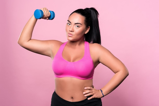 Starting exercises. portrait of young pretty mulatto lady holding dumbbell and posing with arm on hips