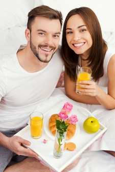 Starting a good day with breakfast in bed. top view of beautiful young loving couple having breakfast in bed and smiling