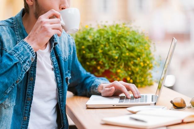 一杯のコーヒーで彼の一日を始めます。コーヒーを飲む若い男のトリミング画像