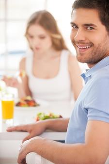 건강한 아침식사로 아침을 시작합니다. 그의 여자 친구와 아침 식사를하면서 어깨 너머로보고 웃는 잘 생긴 젊은 남자