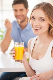 아침을 함께 시작합니다. 오렌지 주스 한 잔을 들고 여자 친구와 아침 식사를 하면서 어깨 너머로 바라보는 잘생긴 젊은 여성