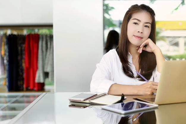 Начиная новый бизнес. красивая азиатская женщина используя цифровые таблетку и компьтер-книжку с улыбкой пока сидящ на магазине одежды.