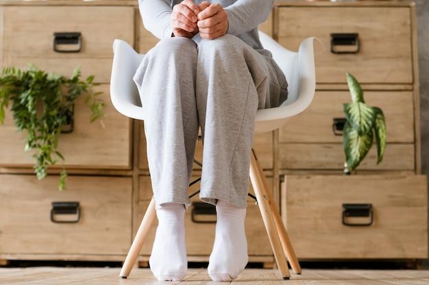 걱정으로 새로운 하루를 시작합니다. 무릎에 주먹으로 의자에 앉아 남자. 발끝.
