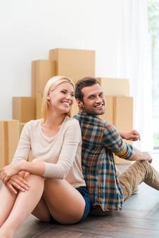 새로운 삶을 함께 시작합니다. 배경에 판지 상자가 놓여 있는 동안 새 아파트 바닥에 앉아 있는 행복한 젊은 커플