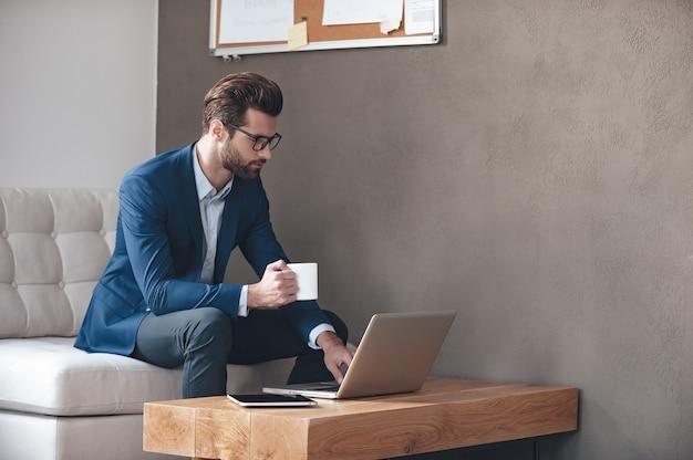 Начало нового рабочего дня. красивый молодой человек в очках держит чашку кофе и работает с ноутбуком, сидя на диване в офисе