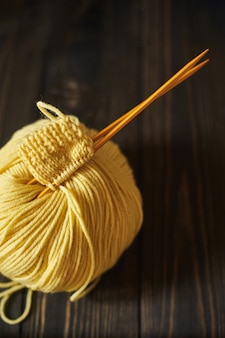 最初の編み物プロジェクトの開始。木製のテーブルに黄色の編み糸と針