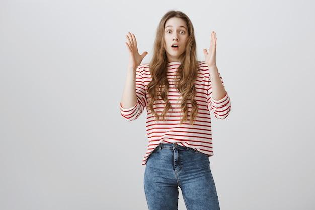 Пораженная и шокированная девушка поднимает руки вверх, задыхаясь от изумления