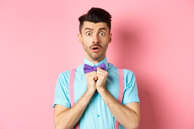 口ひげを生やし、息を切らして息を止め、ピンクの背景の上に立っているオインの蝶ネクタイで驚いて心配している上品な男。