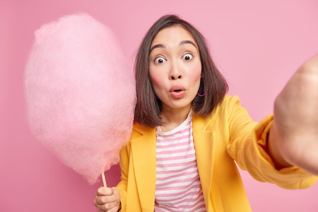 Испуганная азиатская женщина смотрит потускневшими глазами делает фото, на котором она держит вкусную сладкую вату, любит есть что-нибудь сладкое, позирует у розовой стены в стильной одежде
