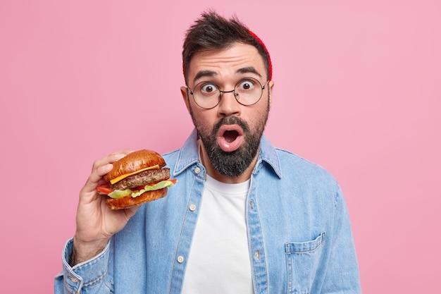 Пораженный бородатый мужчина ест калорийную еду, вкусный гамбургер наслаждается вкусом свежего бургера, одетый в повседневную одежду