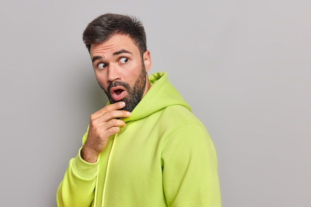 Startled bearded young man holds chin opens mouth from amazement