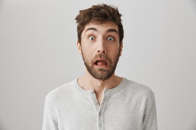 Ragazzo caucasico spaventato che si sveglia mattina, facendo smorfie con i capelli disordinati