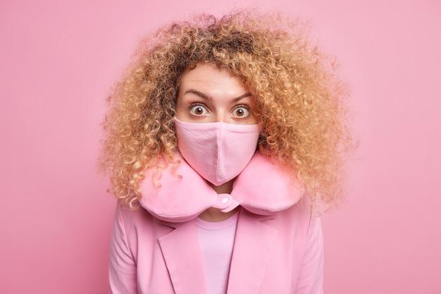 Una donna europea spaventata con i capelli ricci e folti indossa una maschera protettiva durante la pandemia di coronavirus indossa un cuscino per il collo sente qualcosa di scioccante vestita in costume formale posa contro il muro rosa