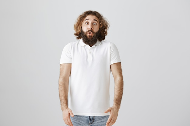 Startled middle-eastern man look astounded, gasping and drop jaw shocked