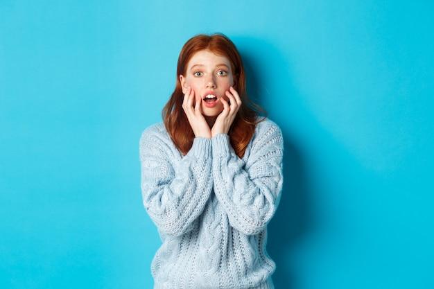 何か素晴らしいものを見つめ、畏敬の念を抱き、青い背景にセーターを着て立っているびっくりした赤毛の女の子