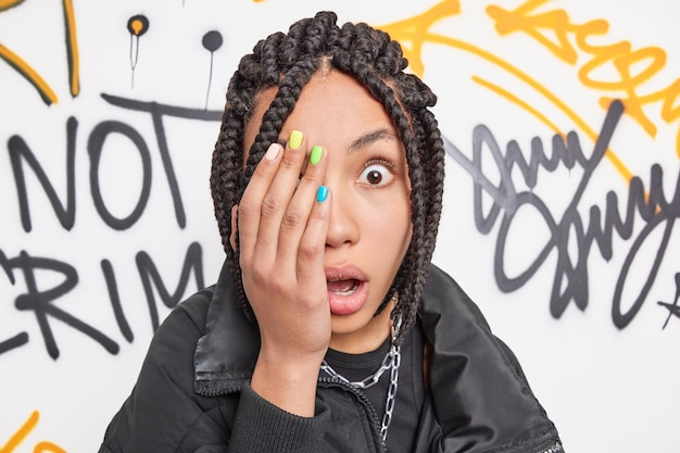 Startled teenage girl covers face with hand stares surprised at camera has colorful nails braided hairstyle reacts on something amazing poses against graffiti wall