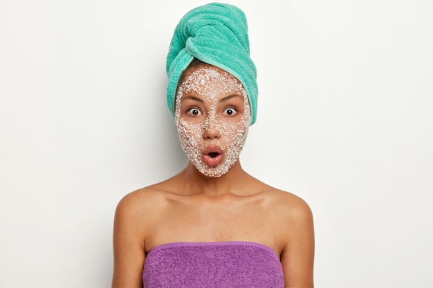 Startled young lady stares with omg expression, has crystal sea salt scrab on face, shocked to have many acnes, wears wrapped towel on head
