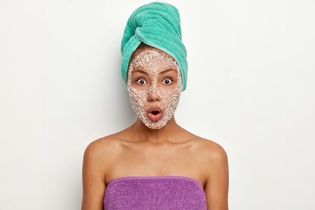 びっくりした若い女性は、omgの表情で見つめ、顔にクリスタルの海塩のスクラブがあり、多くのにきびがあることにショックを受け、頭に包まれたタオルを着ています