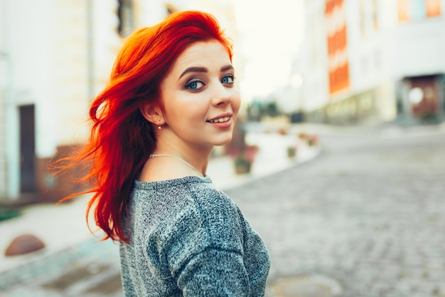 Startled young redhead woman looking back over her shoulder at the camera as she strolls down a deserted urban street