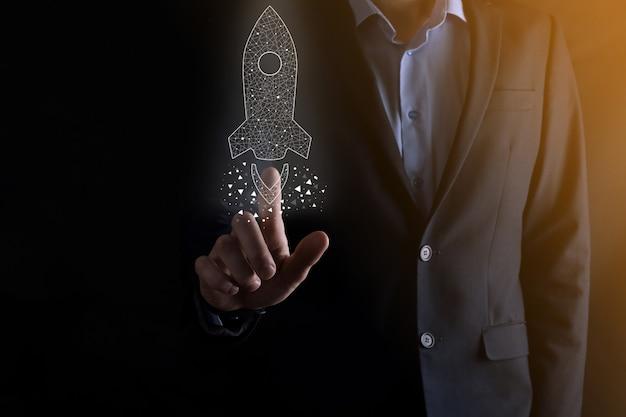 Бизнес-концепция запуска, бизнесмен, держащий значок прозрачной ракеты, запускает и взлетает, вылетая из экрана с сетевым подключением на темном фоне.