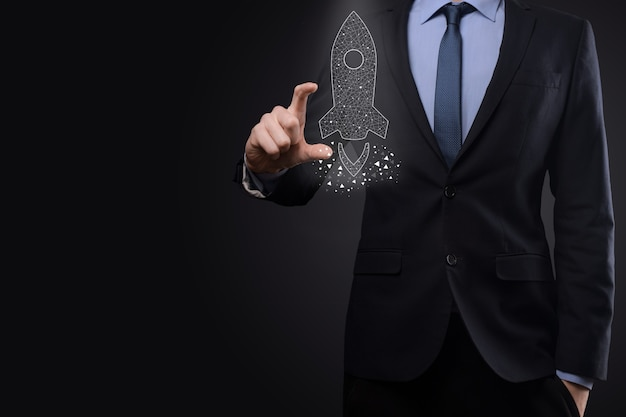 スタートアップのビジネスコンセプト、アイコンの透明なロケットを保持しているビジネスマンが起動し、暗い背景のネットワーク接続で画面から飛び出します。
