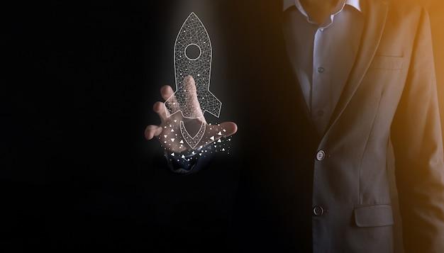스타트업 비즈니스 개념인 아이콘 투명 로켓을 들고 있는 사업가가 어두운 배경에서 네트워크 연결을 통해 화면에서 날아가고 있습니다.