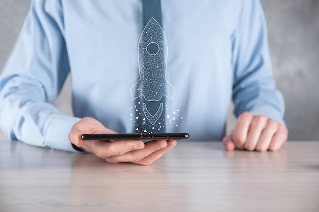 Бизнес-концепция запуска, бизнесмен, держащий значок прозрачной ракеты, запускает и взлетает, вылетая из экрана с сетевым подключением на темной стене.