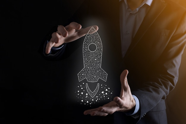 시작 비즈니스 개념, 사업가 아이콘 투명 로켓을 들고 시작 하 고 어두운 벽에 네트워크 연결 화면에서 날아 날아.