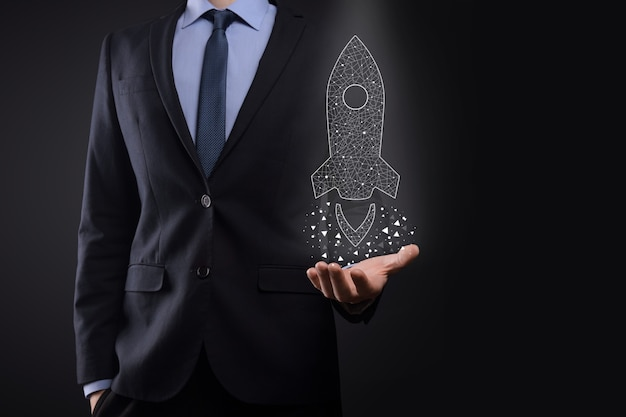 Startup business concept, businessman holding icon transparent rocket is launching and soar flying out from screen with network connection on dark background.