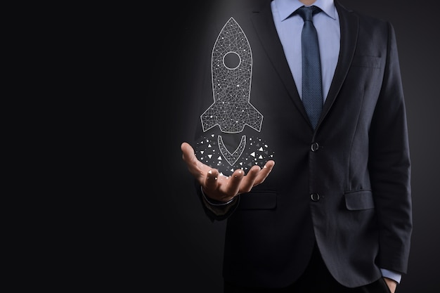 Startup business concept, businessman holding icon transparent rocket is launching and soar flying out from screen with network connection on dark wall.