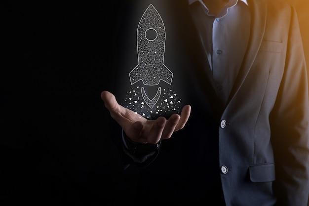 Startup business concept, businessman holding icon transparent rocket
