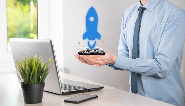 스타트업 비즈니스 개념인 태블릿과 아이콘 로켓을 들고 있는 사업가가 어두운 배경에서 네트워크 연결을 통해 화면에서 날아가고 있습니다.