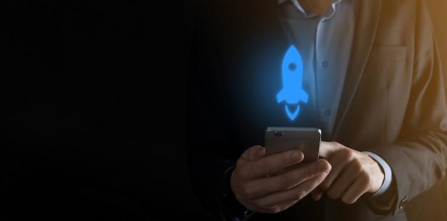 スタートアップのビジネスコンセプト、タブレットとアイコンロケットを保持しているビジネスマンが起動し、暗い背景のネットワーク接続で画面から飛び出します。