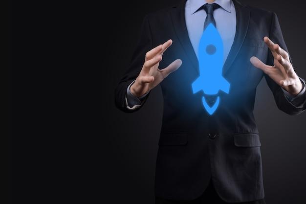 スタートアップのビジネスコンセプト、タブレットとアイコンロケットを保持しているビジネスマンが起動し、暗い表面にネットワーク接続で画面から飛び出して急上昇します
