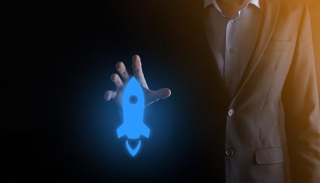 Бизнес-концепция запуска, бизнесмен, держащий планшет и значок, запускает ракету и взлетает с экрана с сетевым подключением на темной стене.