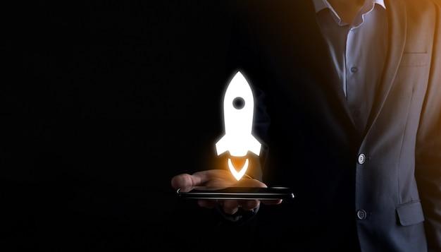 Бизнес-концепция запуска, бизнесмен, держащий планшет и значок, запускает ракету и взлетает с экрана с сетевым подключением