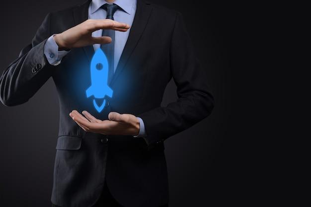 시작 비즈니스 개념, 사업가 태블릿 및 기호 로켓을 들고 시작 하 고 어두운 벽에 네트워크 연결 화면에서 날아 날아.