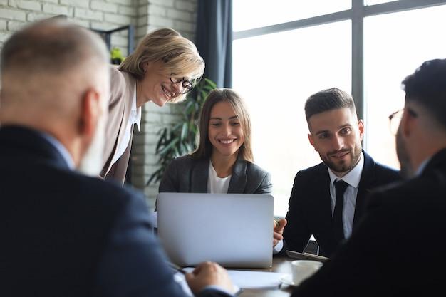 現代の明るいオフィスのインテリアでの会議とラップトップでの作業に関するスタートアップビジネスチーム。